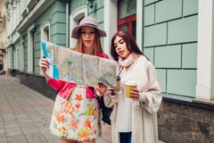Two women tourists searching for right way using map in Odessa. Happy friends travelers showing direction and laughing royalty free stock images