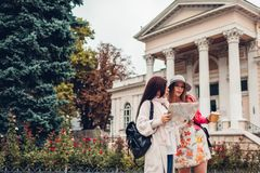 Two women tourists searching for right way using map in Odessa. Happy friends travelers showing direction. And laughing stock photography