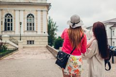 Two women tourists searching for right way using map in Odessa. Happy friends travelers showing direction stock photos