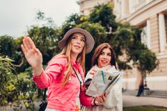 Two women tourists searching for right way using map in Odessa by opera house. Happy friends travelers pointing. On direction stock photo
