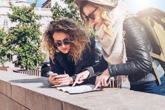 Two women tourists standing on city street and looking for way on destination map and navigation system in smartphone. Two young women tourists are standing on Stock Photos