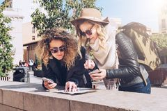 Two women tourists standing on city street and looking for way on destination map and navigation system in smartphone. Two young women tourists are standing on Royalty Free Stock Photo