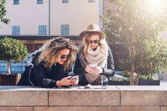Two women tourists standing on city street and looking for way on destination map and navigation system in smartphone. Two young women tourists are standing on Royalty Free Stock Image