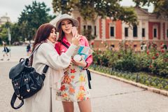 Two women tourists taking picture of architecture in Odessa using phone. Happy friends travelers going sightseeing by stock photography