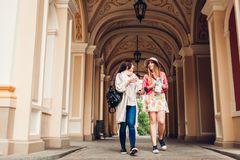Two women tourists talking while going sightseeing by opera house in Odessa. Happy friends travelers using map. And drinking coffee royalty free stock image