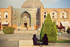 Two women in traditional hijab meeting near historical mosque Masjed-e Sheikh Lotfollah in Isfahan. Royalty Free Stock Photography