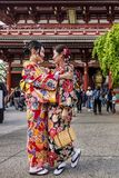 Two women in traditional Japanese clothes hug each other tenderly in the Senso-ji temple in Tokyo, Japan stock image