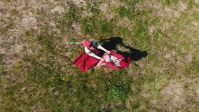 Two women in traditional Russian clothes do the roundelay on the meadow. Aerial view stock video