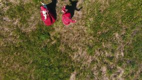 Two women in traditional Russian clothes lead the dance on the green field. Aerial view stock footage
