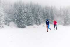 Two women trail running on snow in winter mountains. Girls running together on snow in winter mountains. Sport, fitness inspiration and motivation. Two women Royalty Free Stock Images