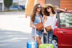 Two women traveling by car. Two young beautiful girlfriend, a brunette with long hair, wearing sun glasses, with fashionable handbags brown, standing near a red Royalty Free Stock Photography