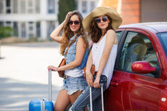 Two women traveling by car. Two young beautiful girlfriend, a brunette with long hair, wearing sun glasses, with fashionable handbags brown, standing near a red Stock Images