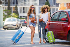 Two women traveling by car. Two young beautiful girlfriend, a brunette with long hair, wearing sun glasses, with fashionable handbags brown, standing near a red Stock Photo