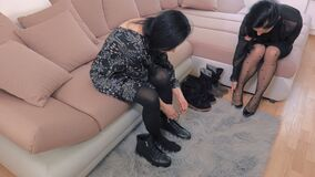 Two women try boots and shoes. In room stock video