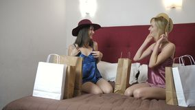 Two women trying on newly bought hats at home. Two beautiful women sitting on bed at home in lingeire and taking out newly bought hats from shopping bags. Dolly stock video