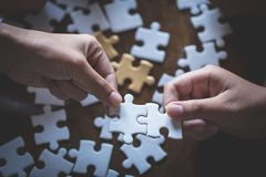 Two women are trying to connect a pair of puzzle pieces. Symbol of association and connection. Concept of business strategy.  royalty free stock photo