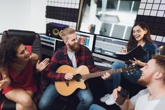 Two women and two men sing a song in a guitar in a modern recording studio. They sit behind the remote control of sound and sing a song. They are having fun Royalty Free Stock Images