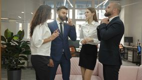 Two women and two men stand in the office and talk, one of the men is talking on the phone, office workers, a metropolis. Offices, office workers 4k stock footage