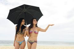 Two women with umbrella on the beach Royalty Free Stock Photos