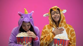Two women in unicorn and giraffe pajamas eating popcorn and watching comedy. Stock footage stock footage
