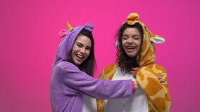 Two women in unicorn and giraffe pajamas laughing and hugging, friendship. Stock footage stock video