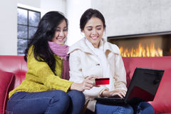 Two women using debit card for shopping online Stock Images