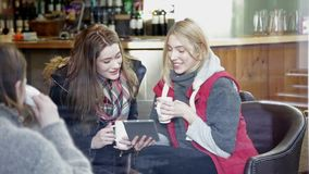 Two women using a digital tablet in a cafe. Two young women are sitting on a sofa in a cafe together. They are talking and using a digital tablet stock video