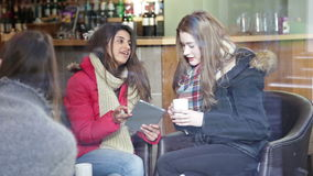 Two women using a digital tablet in a cafe. Two young women are sitting on a sofa in a cafe together. They are talking and using a digital tablet stock video footage