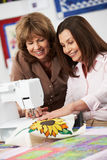 Two Women Using Electric Sewing Machine Stock Images
