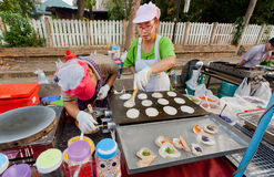 Two women using a gas stove on which preparing pancakes and other food for street fair Royalty Free Stock Photo