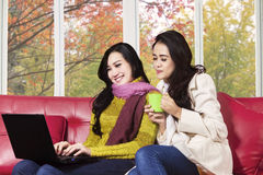 Two women using laptop on sofa Stock Images