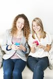 Two women using mobile devices. Two smiling women using mobile devices with colorful cases Royalty Free Stock Images