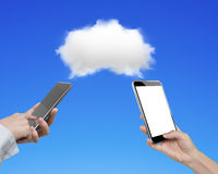 Two women using smart phones with white cloud. Two women using smartphones to exchange information, transferring data from white cloud, on blue background Stock Photos