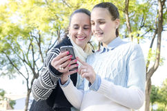 Two women using a smartphone Stock Photography
