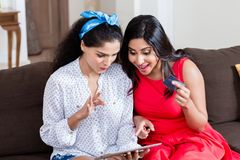 Two women using a tablet PC for online payment. Two young women using a tablet PC for online payment with the credit card Stock Photo