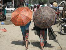 Two Women w/ Umbrellas in Kathmandu, Nepal. These are two women with colorful umbrellas on a sunny day in Kathmandu, Nepal stock photography