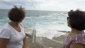 Two women waching how the waves crashing against the stone pier.  stock video footage
