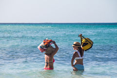 Two women waiting in the sea. Two women with bags waiting for a boat in the sea, Mexico Stock Images