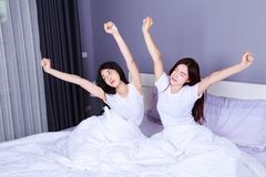 Two woman waking up and hand raised on bed in bedroom Royalty Free Stock Image
