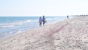 Two women walk along sandy beach in summer. Two women in hats walk along sandy beach away from camera in summer stock footage