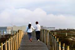 Two Women Walk on a Boardwalk royalty free stock photo