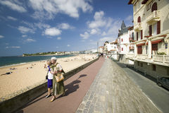 Two women walk down beach boardwalk at St. Jean de Luz, on the Cote Basque, South West France, a typical fishing village in the Fr Royalty Free Stock Photos