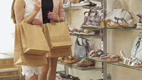 Two women walk at the shoe shop. Two young women walking at the shoe shop. Female friends keeping shopping bags on their arms. Low shot slender girls spending stock footage