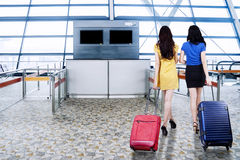 Two women walking in the airport terminal Stock Image