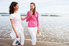 Two Women Walking Along Beach Looking At Mobile Phone Royalty Free Stock Photography