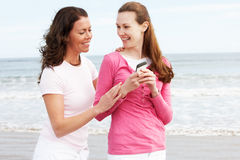 Two Women Walking Along Beach Looking At Mobile Phone Stock Image