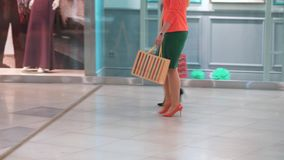 Two women walking along shop windows with shopping bags in hands.  stock footage