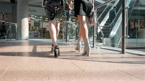 Two women walking along shop windows with shopping bags in hands go to escalator, modern office. Two women walking along shop windows with shopping bags in hands stock footage