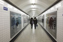 Two women walking along a tunnel. Two women waling side by side along a tunnel of the London Underground Royalty Free Stock Photos