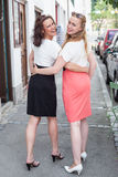Two Women Walking with Arms Around Each Other Royalty Free Stock Image